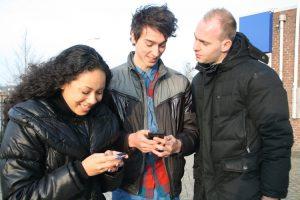 Een groepje jongeren met hun mobiel